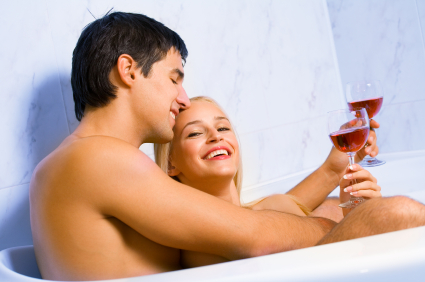 Young happy amorous couple celebrating with redwine at bathroom